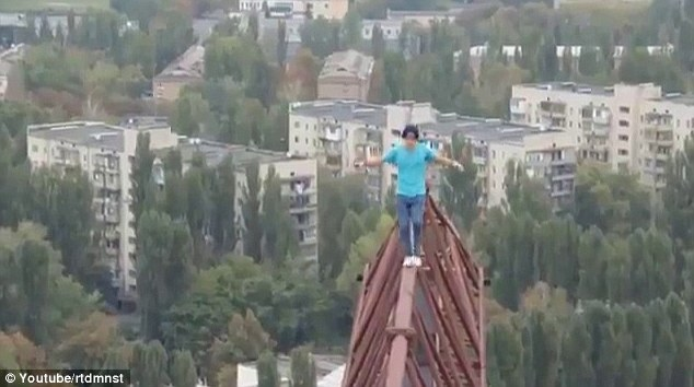 Hundreds of feet above even the roofs of the tower blocks, the fearless youth walks casually along a crane
