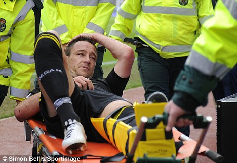 Agony: Terry is carried off with a leg injury at Villa Park