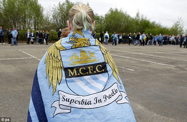 Heading for Wembley: A Manchester City fan prepares to board a coach at the Etihad Stadium heading for Wembley