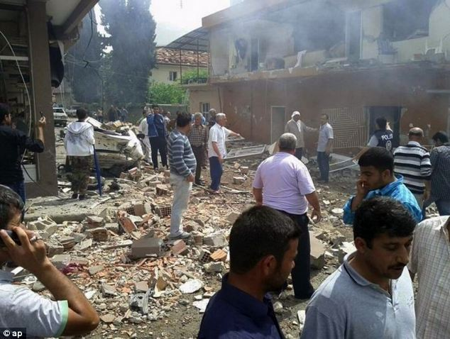 People gather at the site of the double explosion, which has killed at least 30 and injured scores more