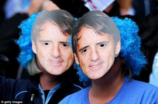 Support: Two Manchester City fans wear Mancini masks at Wembley