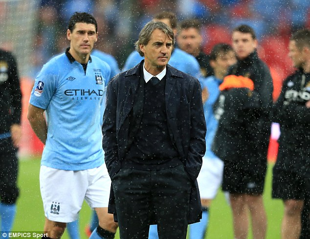 Contrast: Manchester City manager Roberto Mancini looks on after his team lost in the FA Cup Final