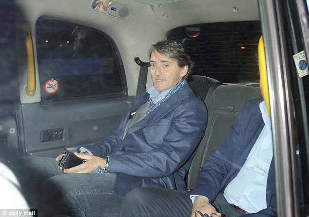 In high spirits: Mancini might have been checking Mail Online while chatting with friends in a taxi