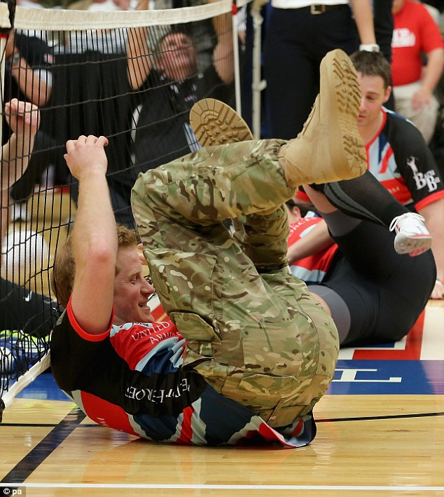 Falling down: Prince Harry plays for the UK team against the USA during a seated volleyball exhibition match