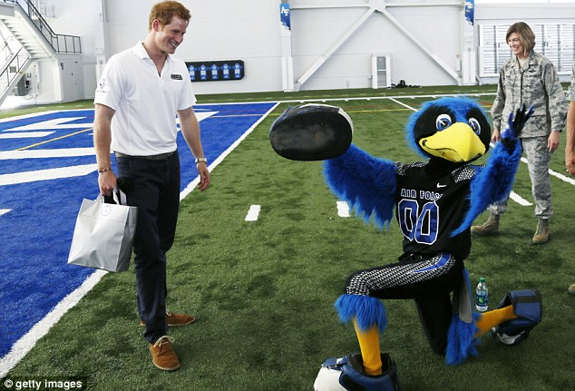 Shoe on the other foot: Prince Harry is presented with a shoe as a gift from the United States Air Force Academy's mascot 'The Bird'