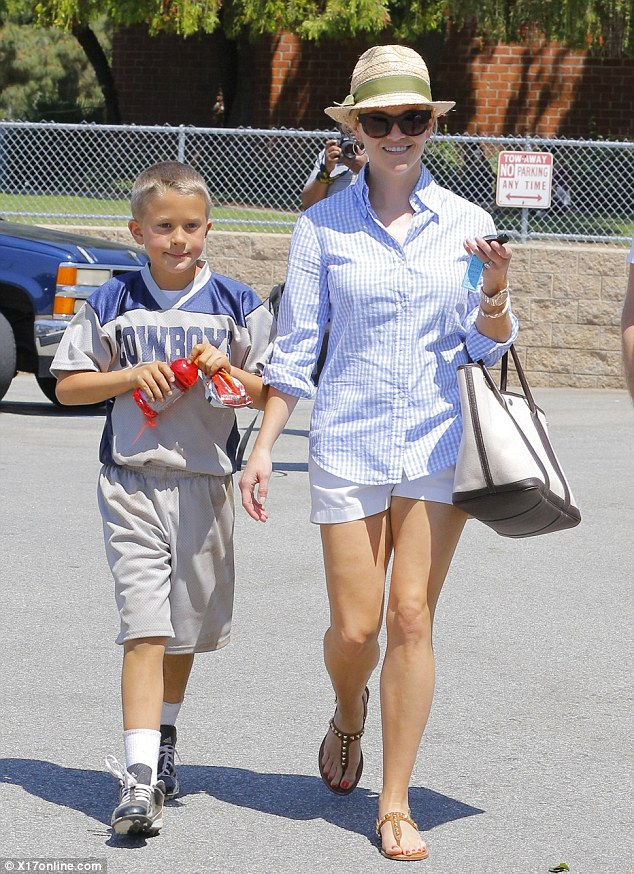 What scandal: The A-lister put on her sweetest smile as she strolled across the parking lot with her son