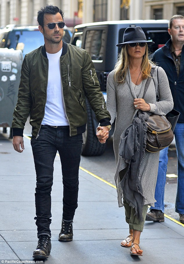 Isn't it romantic: Jennifer Aniston and fiance Justin Theroux held hands as they enjoyed a romantic date in New York on Sunday