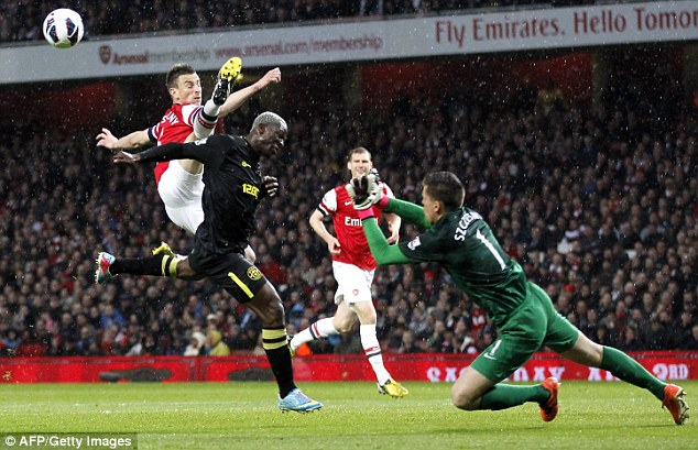 Reach out: Arsenal's Laurent Koscielny (left) clears the ball in front of Wigan's Arouna Kone
