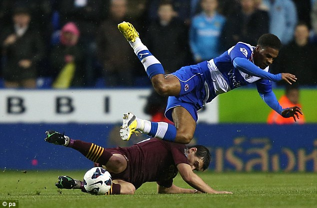 Sliding through: Manchester City's Gareth Barry (left) tackles Reading's Garath McCleary