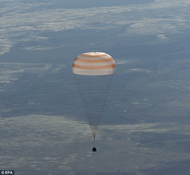 Coming home: This NASA pictures shows the capsule floating to Earth on the barren steppes of Kazakhstan