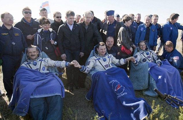 Home again: Hadfield, left, Russian Flight Engineer Roman Romanenko, center, of the Russian Federal Space Agency and NASA Flight Engineer Tom Marshburn
