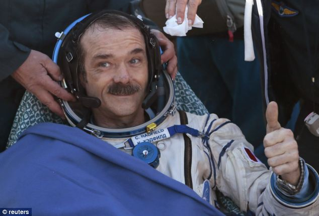 Canadian astronaut Chris Hadfield gestures with a thumbs up after the Russian Soyuz space capsule landed some 150 km (90 miles) southeast of the town of