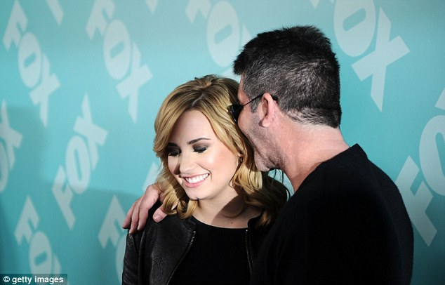Sweet nothings: Cowell cosied up for photographs with the Skyscraper singer and at one point was seen secretively whispering into her ear