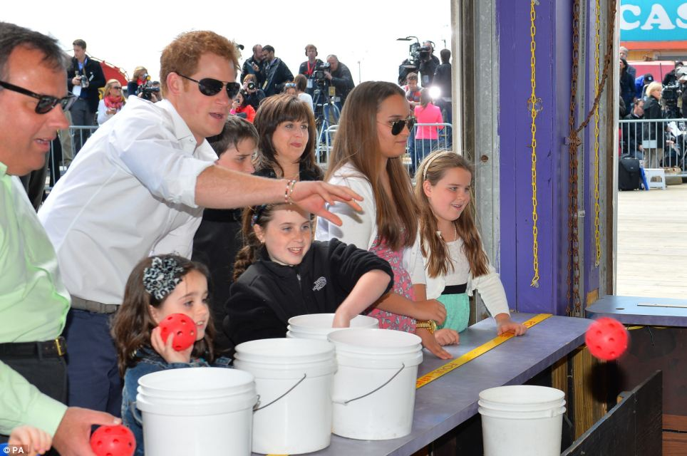 Getting involved: Prince Harry was joined by the governor's children and wife Mary during the tour