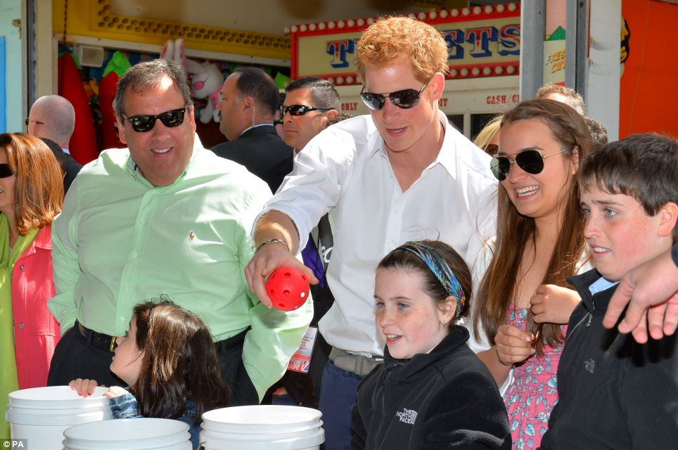 Settling in: Harry tries his hand at a stall in Mantoloking as he is joined by Chris Christie and his family