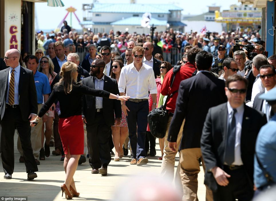 Main attraction: Harry is watched by swarms of people as he visits the Jersey shore on Tuesday