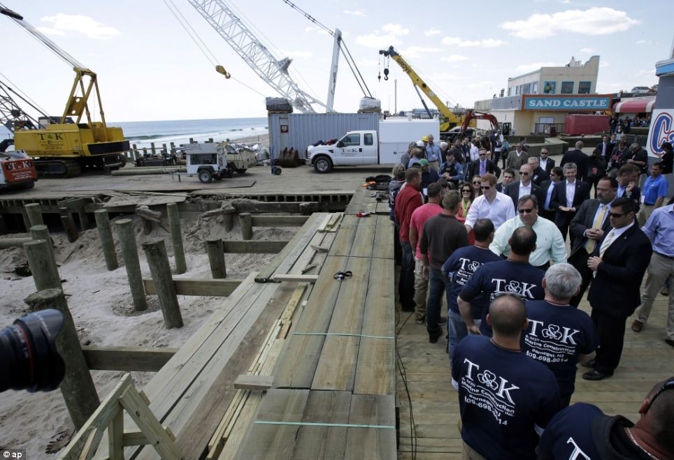 Progress: Prince Harry, center, and New Jersey Gov. Chris Christie greet workers rebuilding the boardwalk while visiting the area hit by Superstorm Sandy