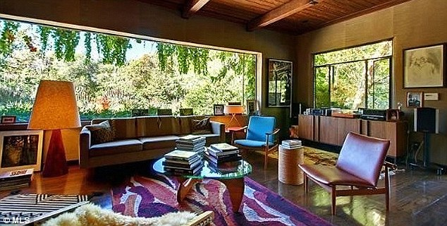 Rich decor: A living room is outfitted in 1970s accents including mahogany furniture and a vibrant rug