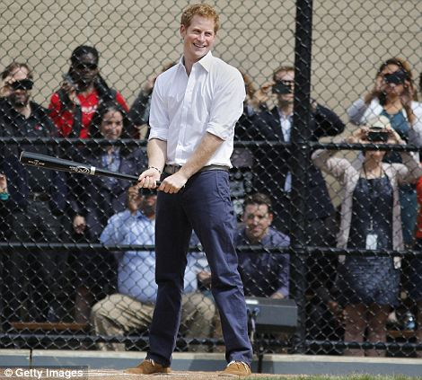 Giving it a go: Harry, who was still wearing a suit after attending an event to promote British businesses, smiles before hitting at the baseball field