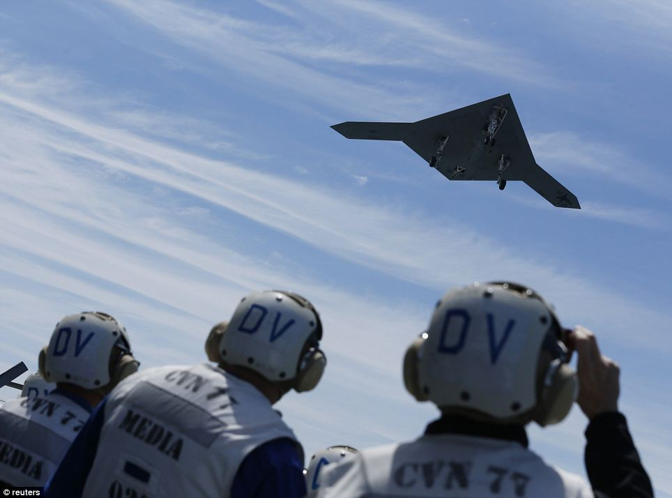Awesome: Reporters wearing U.S. Navy-issued protective gear peer up as the X-47B makes a pass over the deck of the George H. W. Bush in the clear morning skies