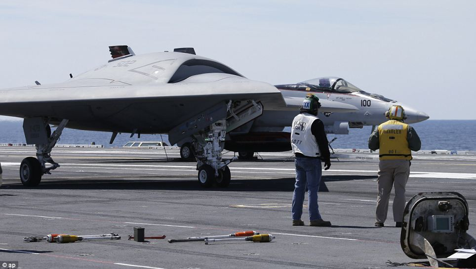 An X-47B drone taxis in front of an F/A18 fighter plane as it is prepared for take off: The aircraft is as yet not equipped with military hardware, but is designed for ample space to accommodate bombs and surveillance equipment