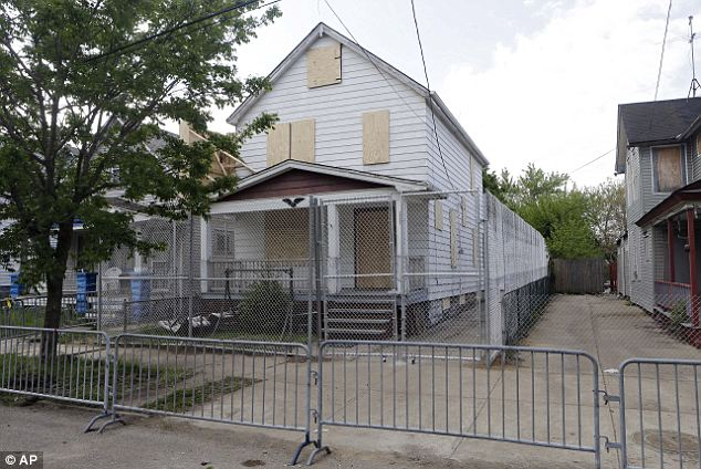 Crime scene: A 10-foot fence has been erected around Ariel Castro's now-boarded up house on Seymour Avenue