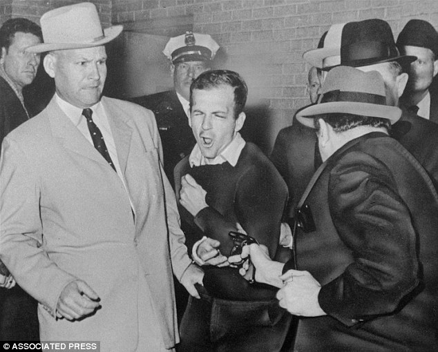 Lee Harvey Oswald, assassin of President John F. Kennedy, reacts as Dallas night club owner Jack Ruby, foreground, shoots at him from point blank range in a corridor of Dallas police headquarters. At left is Detective Jim Leavelle
