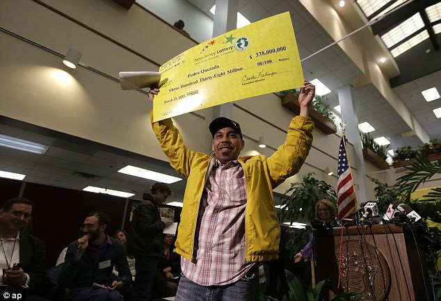 Last big win: Pedro Quezada, the winner of a $338 million Powerball jackpot in March, holds up a promotional check in New Jersey following his big win
