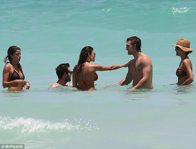 Buff body: One young lady seemed particularly enthralled by the 23-year-old actor's bulging bicep, giving him a cheeky squeeze as the group of friends frolicked in the ocean
