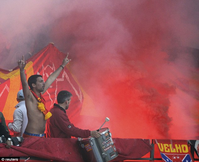 Ultras: One Benfica fan cheers his team on topless as a flare is let off