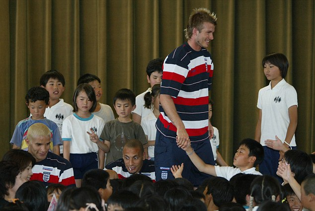 Mobbed: Beckham was the centre of attention during the World Cup in Japan and was followed everywhere
