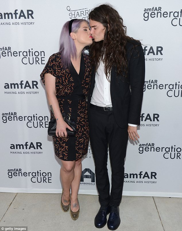 Sealed with a kiss: Kelly Osbourne and her beau Matthew Mosshart enjoyed a kiss on the red carpet at amfAR's generationCURE party on Wednesday night