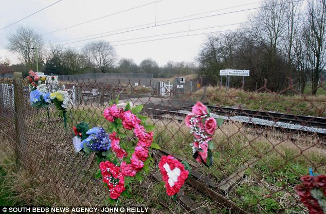 A pair of headphones, an iPod Nano and her Blackberry phone were found next to Katie's body at the crossing. Pictured are flowers from a previous death at the crossing