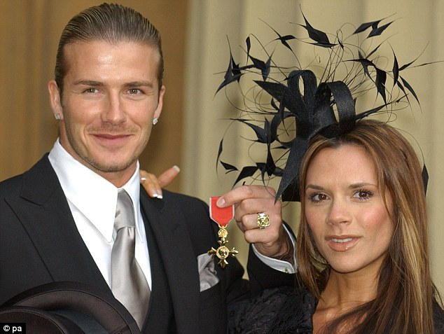 Decorated: David Beckham with his wife Victoria at Buckingham Palace as he is awarded an OBE