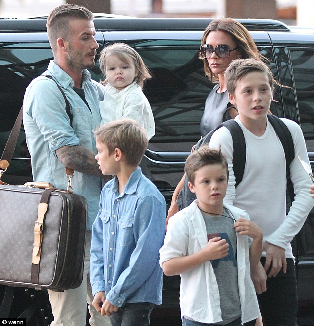 Happy family: Beckham and his wife Victoria, pictured with their four children Romeo, Cruz, Harper and Brooklyn at Los Angles airport last July