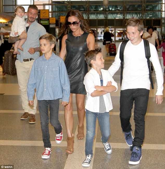 Family man: Beckham at the airport with his four children Romeo, Cruz, Harper and Brooklyn and wife Victoria