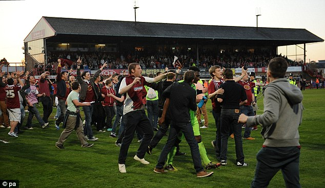 Jubilant: Northampton Town fans invade the pitch as they celebrate their side reaching the play-off final