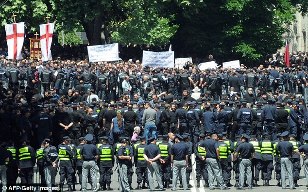 Homophobic: Georgian police officers cordon off the area in central Tbilisi where Orthodox believers and anti-gay activists demonstrate to protest gay rights activists' plans to stage a rally marking the International Day Dgainst Homophobia