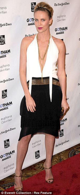 Charlize Theron wears a daring ensemble: a top with a plunging neckline and killer heels