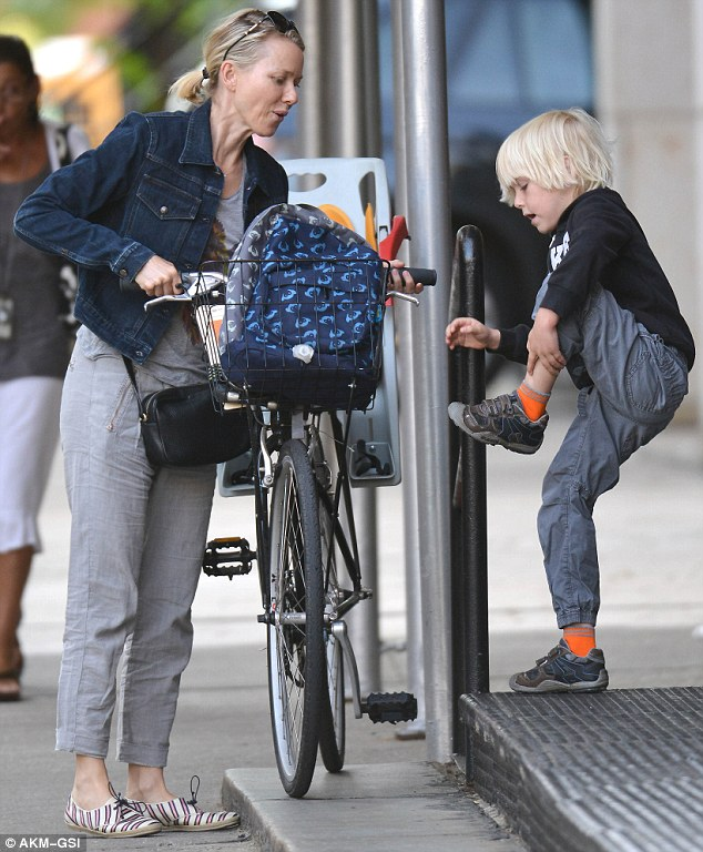 You can do it! Noami watched carefully as her blonde boy steadily balanced to get into his child seat