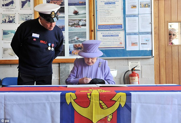 Notable entry: The Queen signs the visitors book accompanied by coxswain Paul Whiston during a visit to the RNLI station in St Ives