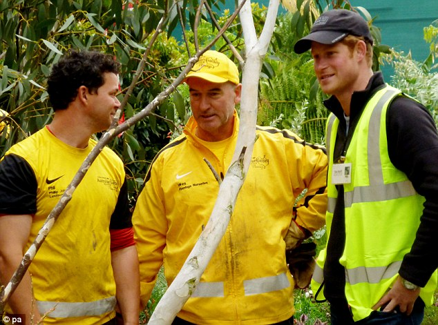 Fitting in in yellow: The royal chats to Phil Johnson, left, and Wes Fleming, centre, at the Trailfinders garden