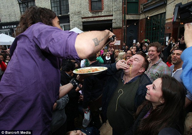 Feed me! Russell feeds spaghetti to members of the public