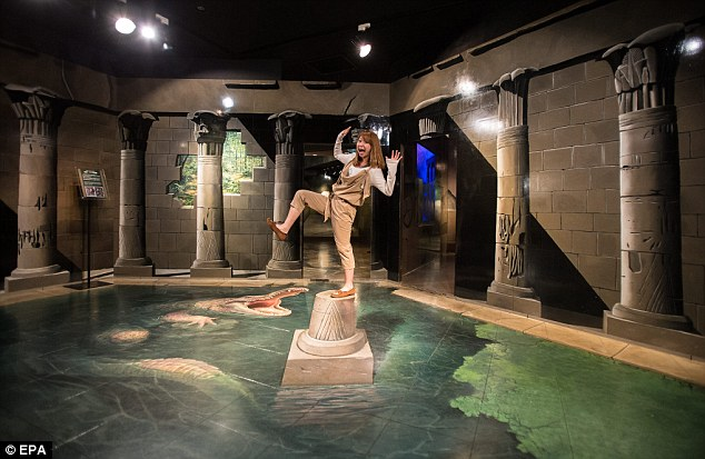 Detailed: A Japanese woman poses for a photo inside the Takao Trick Art Museum. The optical illusion is in fact a mural