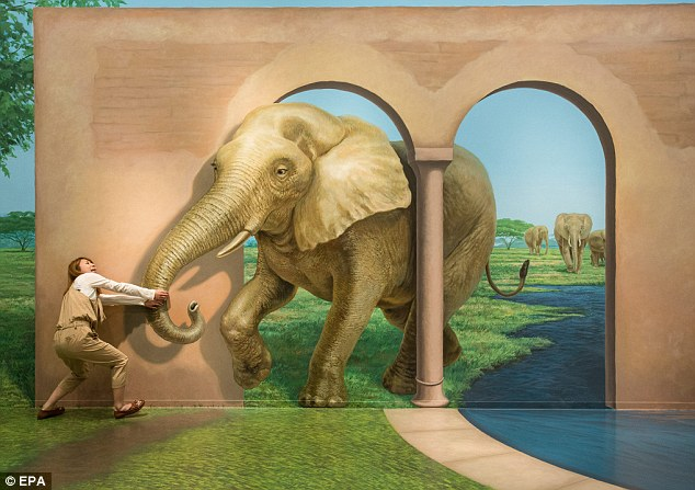 Trick of the eye: A Japanese woman pretends to pull the trunk of an elephant which is in fact a mural painted on a wall