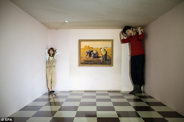 The room is actually trapezoid in shape. The woman on the left hand side is standing in a corner that is much further away than the woman on the right