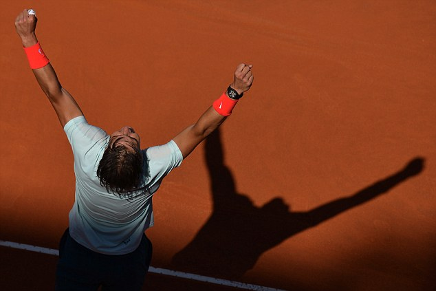 Glory boy: Nadal holds his arms in the air after securing the win over Federer