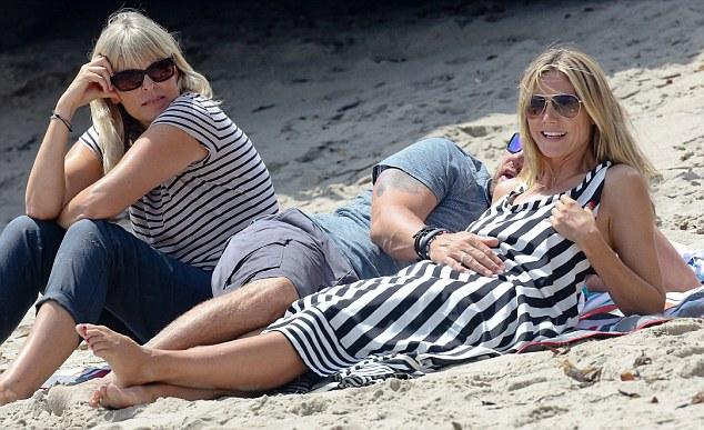 Possessive: Martin kept a hand on Heidi's toned tummy while she enjoyed the ocean view