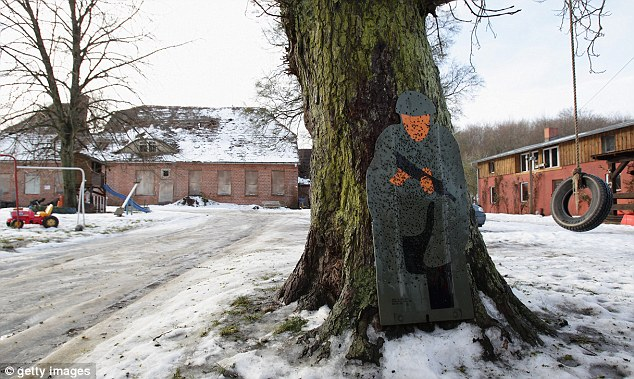 Chilling: A human-shaped target, riddled with holes, rests against a tree in Jamel