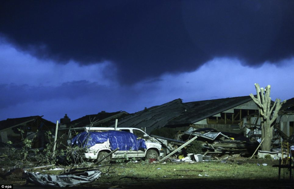 Destroyed: As dawn breaks on Tuesday, storm clouds roll in over a destroyed neighborhood the day after a tornado hit in Moore, Oklahoma,